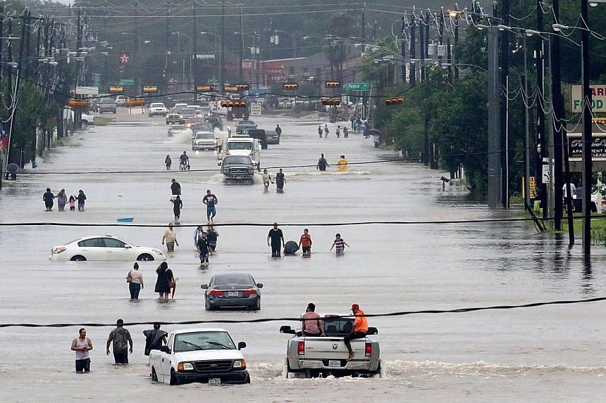People walking through the flooded waters of Telephone Road in Houston during tropical storm Harvey on Aug 27, 2017.