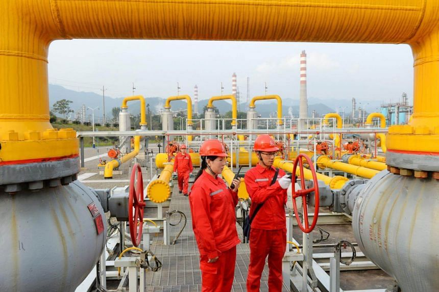 Workers inspect pipelines at a natural gas facility run by Sinopec in Dazhou, Sichuan province, China on Nov 1, 2017.