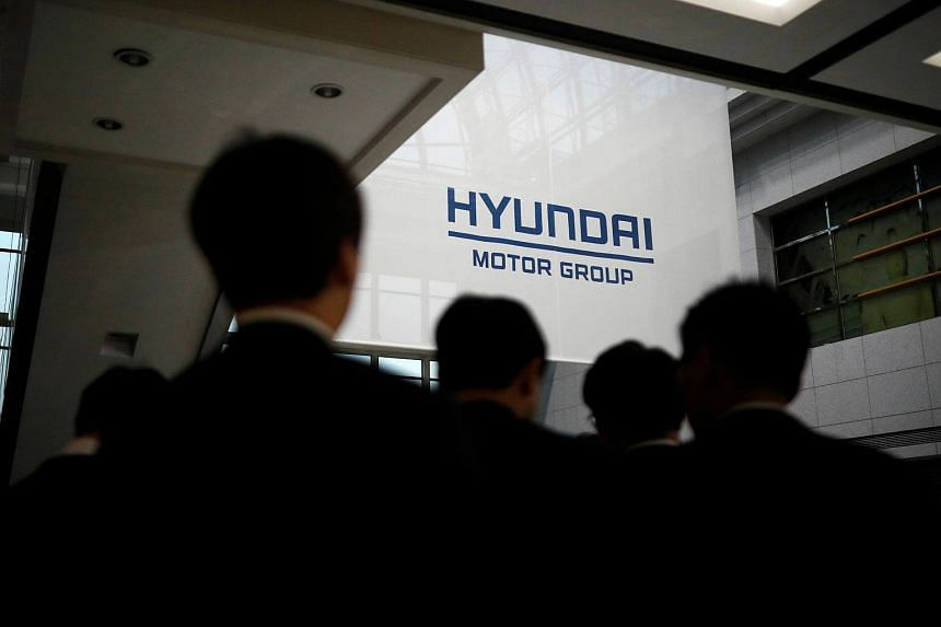 Employees of Hyundai Motor walk past the company's logo after its new year ceremony in Seoul, South Korea, on Jan 2, 2018.