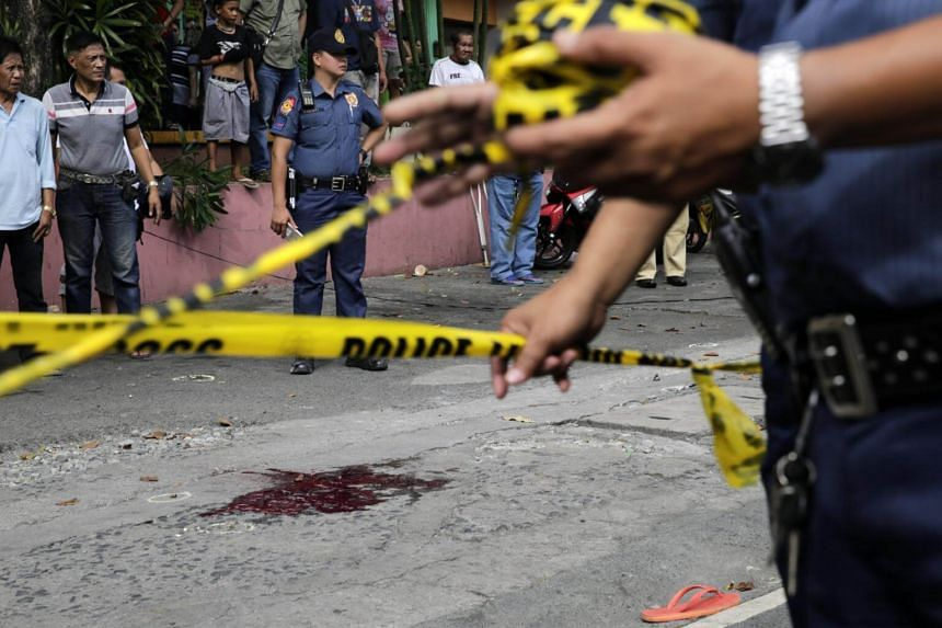 """Filipino policemen at a crime scene where somebody was shot in an alleged """"extra judicial killing"""" in Manila on Jan 5, 2018."""