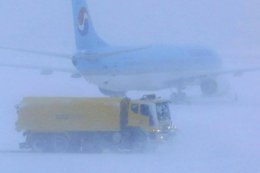 A snowplough clearing snow on a runway at Jeju International Airport, after the island was hit with heavy snowfall, on Jan 11, 2018.
