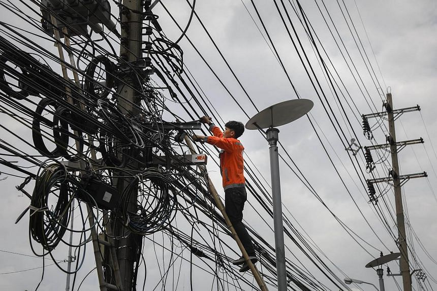 A workers cutting cluttered overhead power lines in Bangkok, Thailand, on Sept 25, 2017.