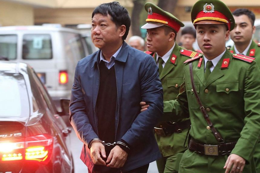 Vietnamese police officers escorting former PetroVietnam chairman Dinh La Thang to the Hanoi People's Courthouse on Jan 8, 2018.