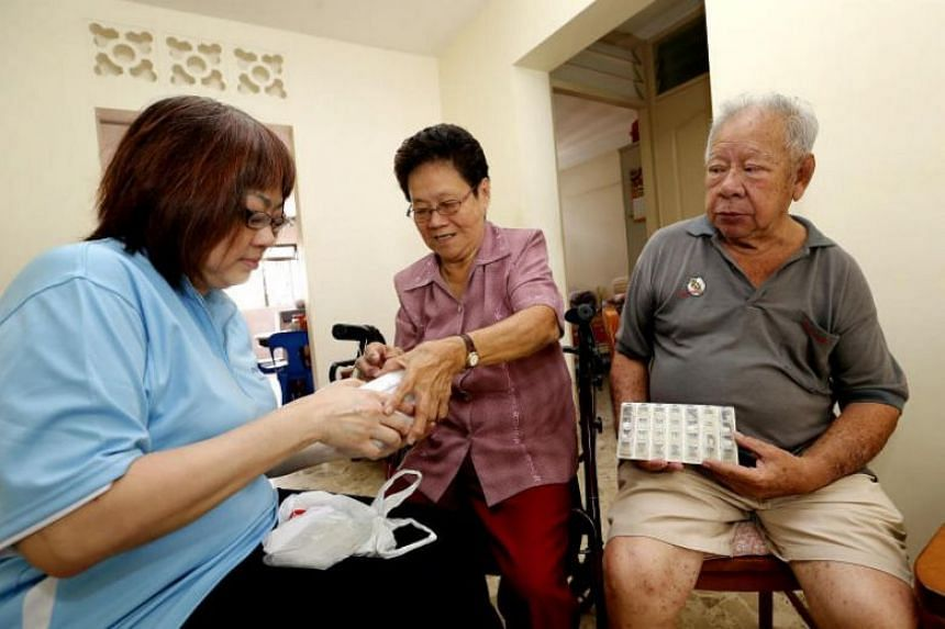 Volunteer Joanna Fang checking on medication for Mr Low Buck Chua, 76, and his wife Dolly, 76, in February 2015.