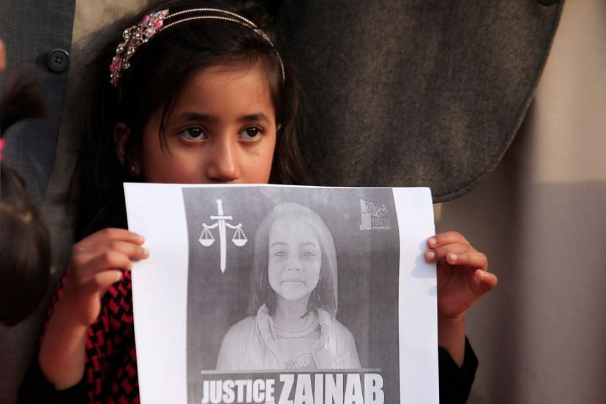 A girl holds up a picture of Zainab Ansari during a protest in Islamabad, Jan 11, 2018.