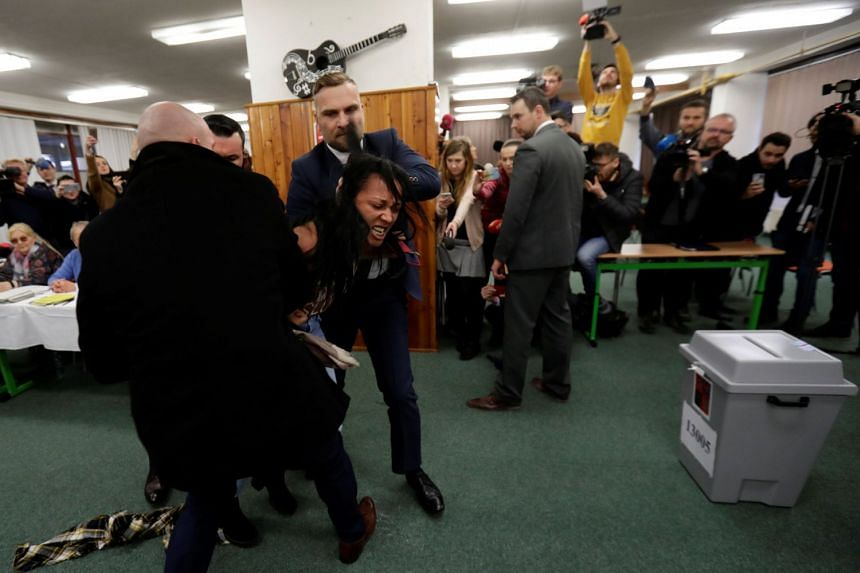 A Femen activist clashes with Zeman's bodyguards at the polling station.