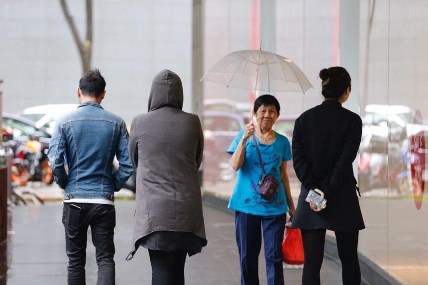 People wearing jackets and coats walk along Orchard Road.