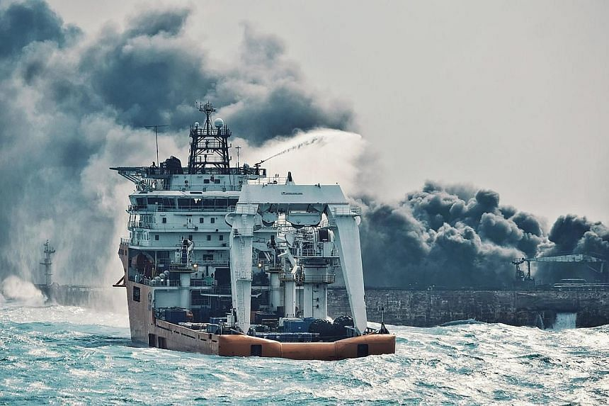 A Chinese offshore supply ship spraying foam on the burning Sanchi oil tanker off the coast of eastern China on Wednesday. The Iranian tanker, which collided with a freight ship and burst into flames last Saturday, remains at risk of exploding and si