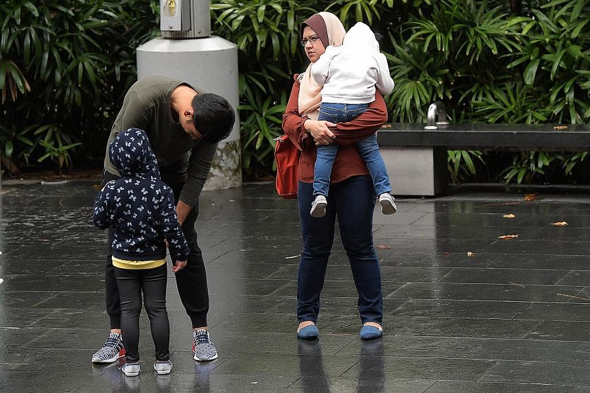A father helping his child with a sweater as they walked down Orchard Road yesterday. The low temperatures have been attributed to a monsoon surge in the South China Sea. House of Seafood, which faces the sea in Punggol, has had to use machines to bl