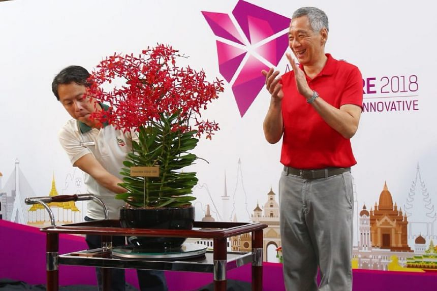 Prime Minister Lee Hsien Loong naming a new orchid Renanthera Asean 2018 with National Parks Board chief executive Kenneth Er.