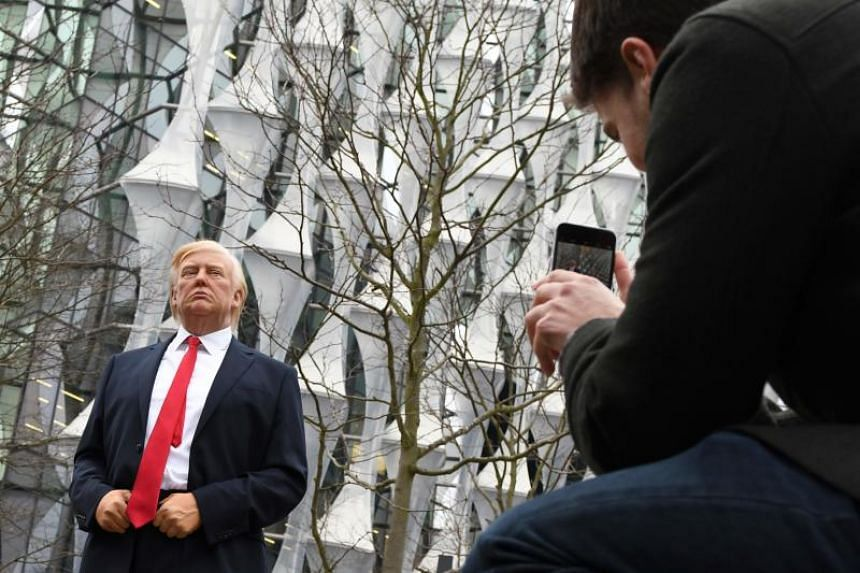 Pedestrians take pictures of a Madame Tussauds wax figure of US President Donald Trump outside the new US Embassy in Embassy Gardens in south-west London on Jan 12, 2018.