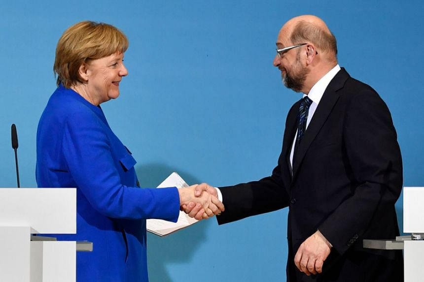 """German Chancellor Angela Merkel and Social Democratic Party leader Martin Schulz told a news conference they were optimistic that a new """"grand coalition"""" could be formed."""