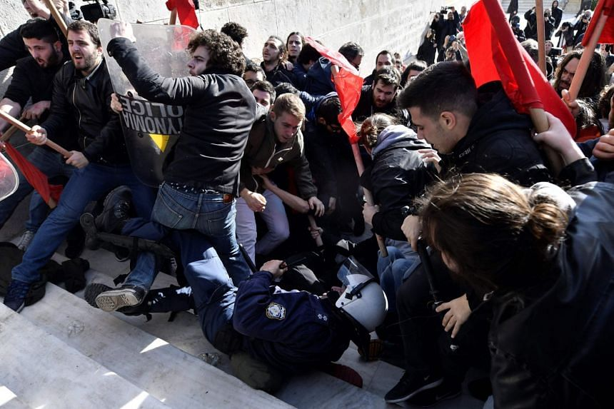 Demonstrators clash with police as they try to take the stairs leading to the parliament building in Athens on Jan 12, 2018, as part of a strike wave against changes to a 36-year-old industrial action law demanded by the country's creditors.
