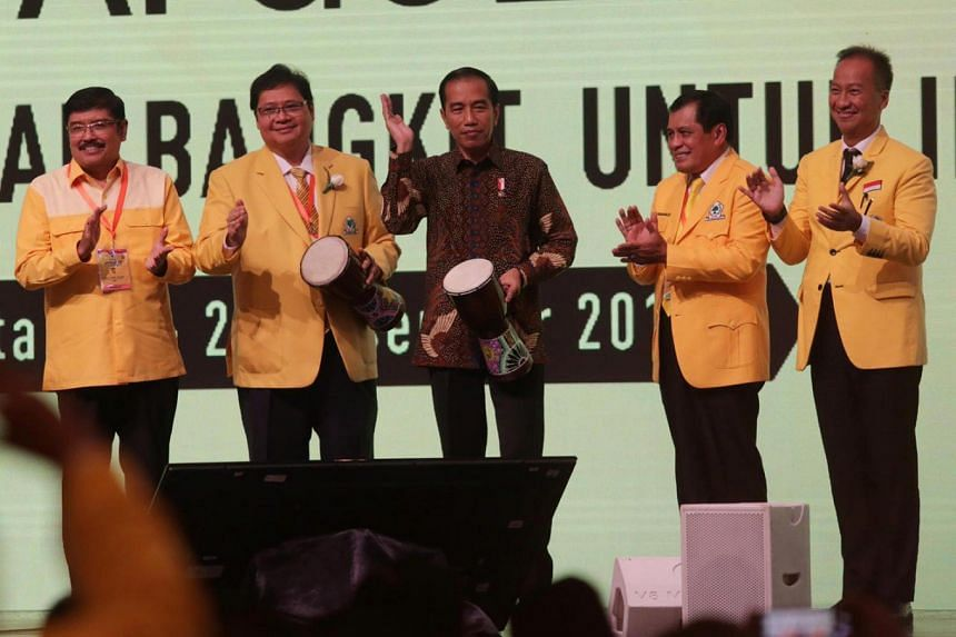 Indonesian President Joko Widodo (centre), with Golkar Party politician Ibnu Munzir (left), newly-elected party chairman Airlangga Hartarto (second left) and two other Golkar politicians, Nurdin Halid (second right) and Agus Gumiwang Kartasasmita (ri