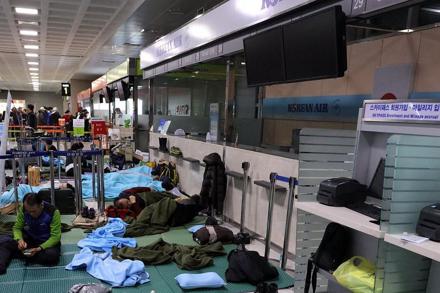 Tourists sleep in the lobby of Jeju International Airport after heavy snow and strong winds caused hundreds of flight cancellations and delays in Jeju, South Korea on Jan 12, 2018.
