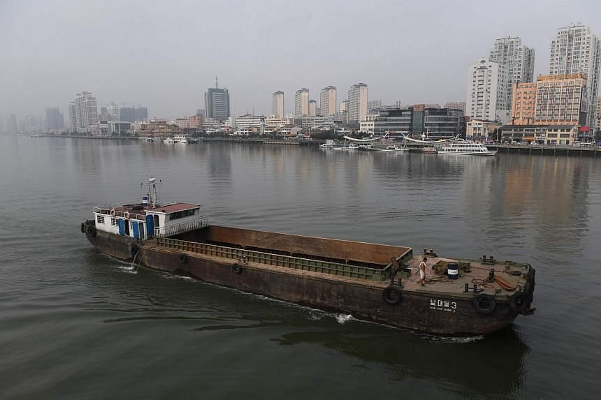 A North Korean ship passes in front of the waterfront of the Chinese border city of Dandong (at rear), opposite the North Korean town of Sinuiju on Sept 4, 2017.