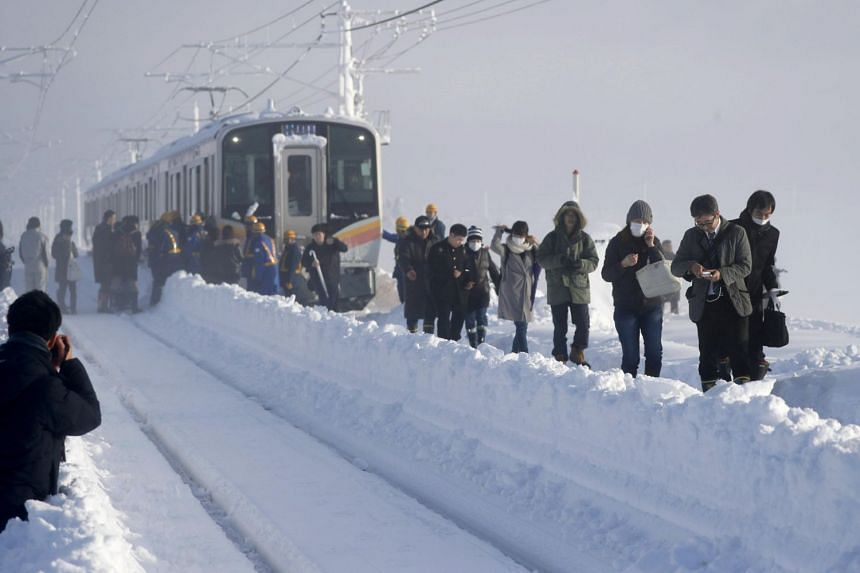 Passengers alight a train on East Japan Railway Co.'s Shinetsu Line, where they spent the night after it was stranded between stations due to heavy snowfall, in Sanjo, Niigata Prefecture, on Jan 12, 2018.
