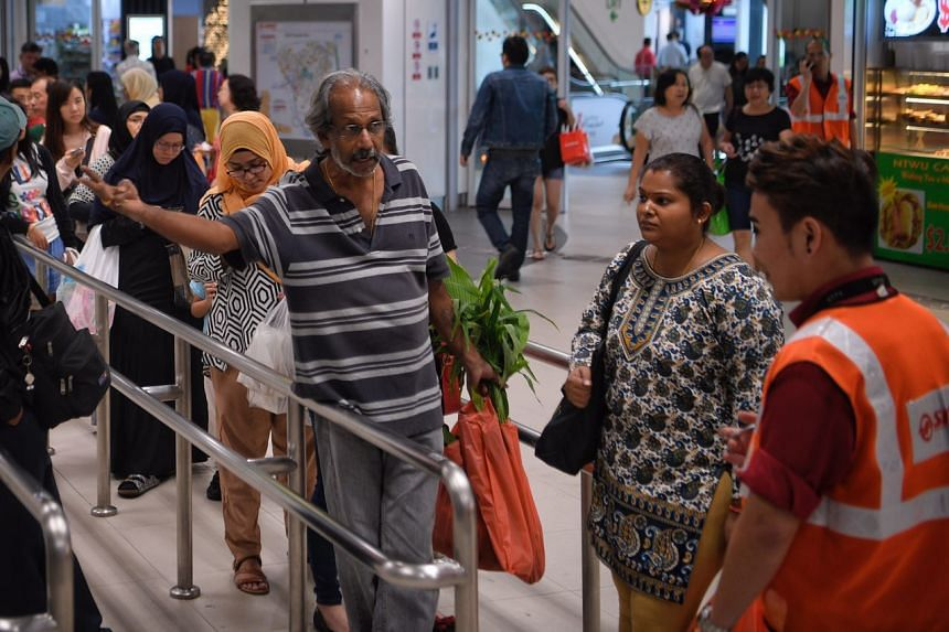 A frustrated commuter speaks with a SMRT staff while waiting for the shuttle service on Jan 12, 2018.