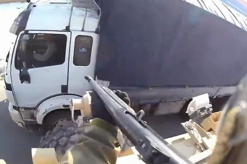 A screenshot from the video shows a gun being pointed at a truck window, which then shatters. The fate of the driver is not known.