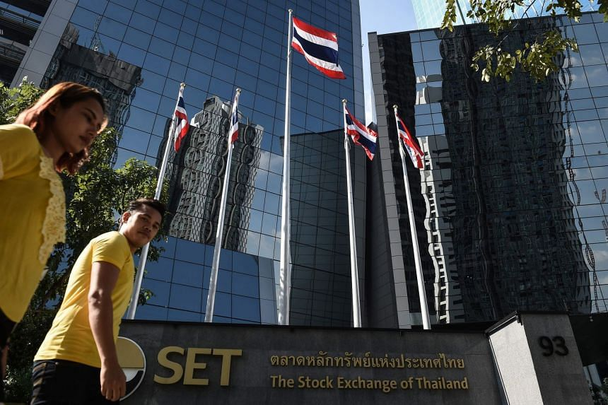 People walk past Thai flags outside of the Stock Exchange of Thailand in Bangkok, on Jan, 8.