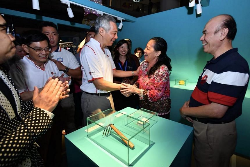 Prime Minister Lee Hsien Loong greeting Madam Wong Lai Ngoh, 66 and Mr Yee Kai Him, 66, at the 'A Good Thing' Exhibition.