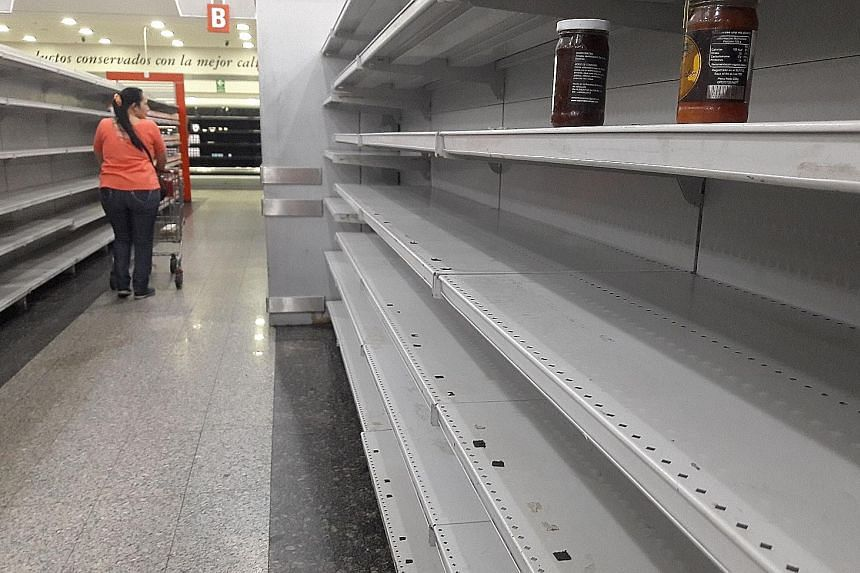 Empty shelves in a supermarket in Caracas on Thursday. Food shortages and hyperinflation have left millions of Venezuelans hungry.