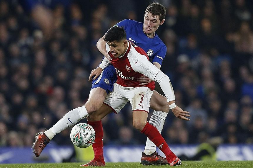 Arsenal forward Alexis Sanchez tussling with Chelsea defender Andreas Christensen during the first leg of their League Cup semi-final on Wednesday. The Chilean looks set to end his stay at the Emirates, with Manchester City and Manchester United both