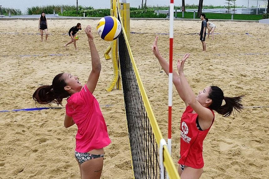 National beach volleyball players Serene Ng (left) and Vanessa Lim training at the Singapore Sports Hub even as temperatures hit lows of 22 deg C on Thursday. Six players are competing for two spots on the Commonwealth Games team, should the Singapor