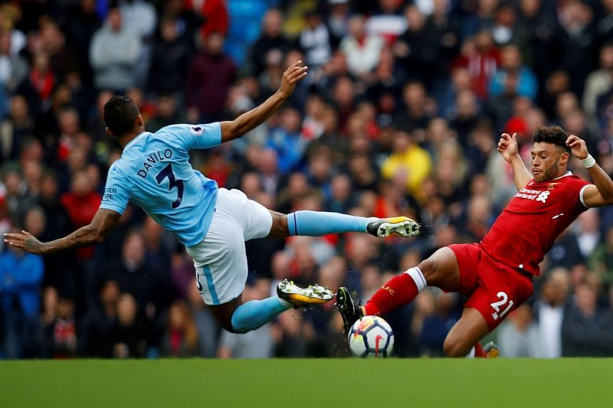 Manchester City's Danilo in action with Liverpool's Alex Oxlade-Chamberlain during the English Premier League match between Manchester City and Liverpool in Manchester, Britain, on Sept 9, 2017.