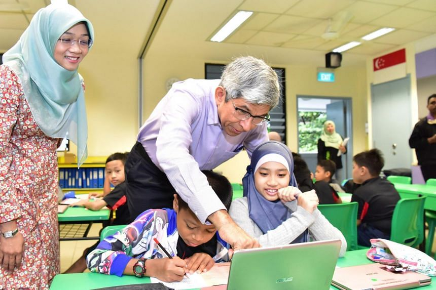 Yayasan Mendaki chief executive officer Rahayu Buang and Minister for Communications and Information Yaacob Ibrahim interact with students under the Mendaki Tuition Scheme at at Northland Primary School.