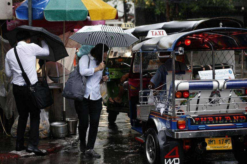 People taking cover under umbrellas as they commute on a rainy morning in Bangkok, on Jan 10.
