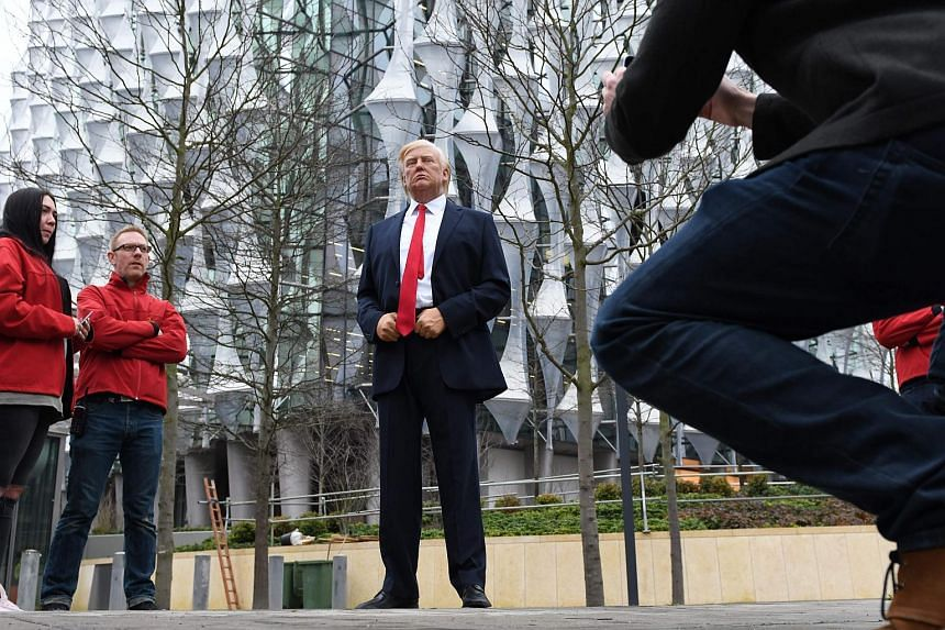 Pedestrians take pictures of a Madame Tussauds wax figure of US President Donald Trump outside the new US Embassy in Embassy Gardens in south-west London, on Jan 12, 2018.