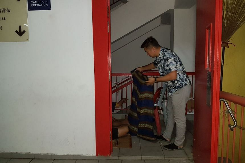 Mr Francis Ng giving out a blanket to a man resting at a staircase landing in Chinatown Complex.
