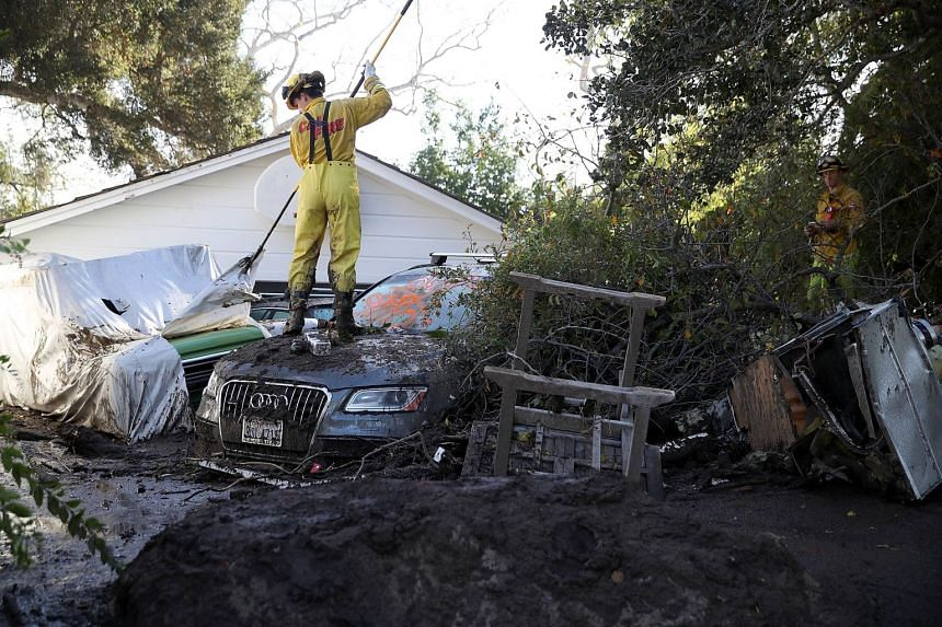 A fire-fighter checks cars next to a home that was destroyed by the mudslides on Jan 12, 2018.