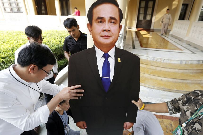 Government officials install a life-size cardboard replica depicting Thai Prime Minister Prayut Chan-o-cha during preparations for the National Children's Day event at the Government House in Bangkok.