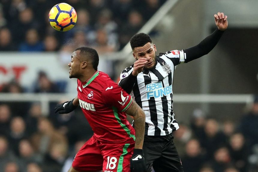 Swansea City's Jordan Ayew in action with Newcastle United's Jamaal Lascelles.
