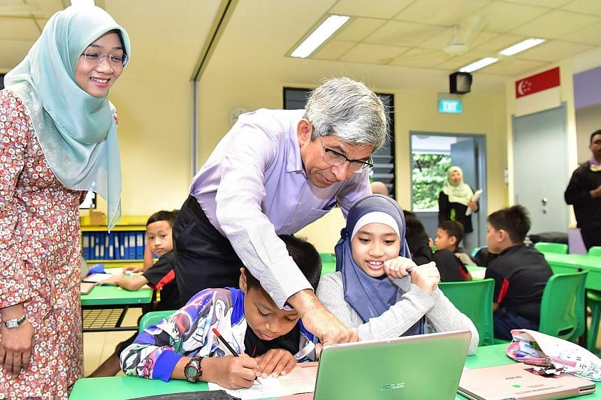 Communications and Information Minister Yaacob Ibrahim interacting with pupils under the Mendaki Tuition Scheme at Northland Primary School yesterday, as Yayasan Mendaki CEO Rahayu Buang looks on.
