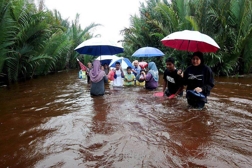 Villagers from Kampung Palong in Pekan district, Pahang, wading through flood waters yesterday to get to the main road. The road in an oil palm estate has been flooded for the past three days.