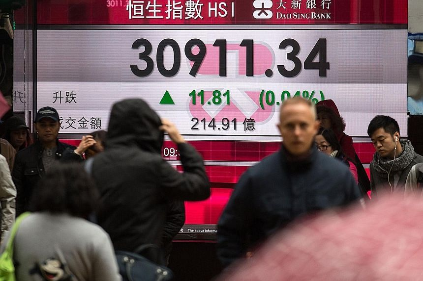 UOBAM head of multi-asset strategy Anthony Raza said shares can still be expected to return 8 per cent to 10 per cent, but bond prices may be hurt, as interest rates are expected to go up. A board displaying the Hang Seng Index. It will be at least t