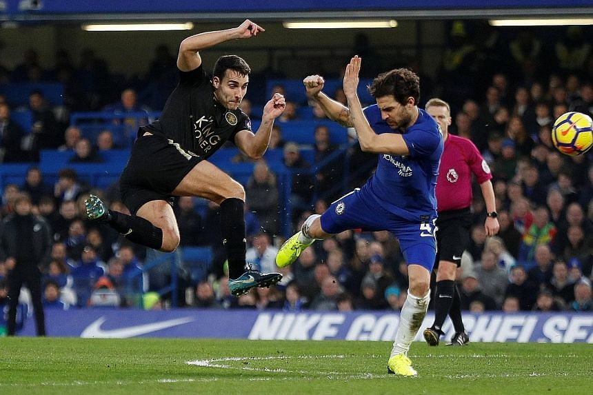 Chelsea's Cesc Fabregas attempting to block a shot from Leicester's Matty James during their 0-0 English Premier League draw at Stamford Bridge yesterday. The Foxes ended with 10 men after Ben Chilwell's second yellow card. The draw was the Blues' fo