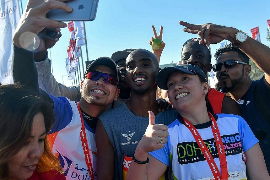 Mo Farah showing (Mobot) love to the spectators after his 10,000m victory at the 2016 Rio Olympics. Four-time Olympic gold medallist Mo Farah (centre) posing for photographs on Friday after the annual Doha Marathon in Qatar. The Briton plans to compe
