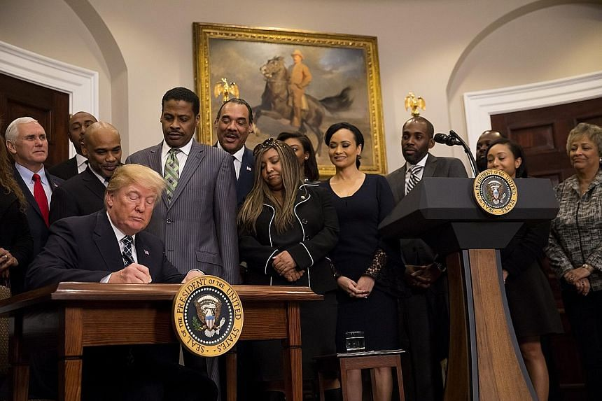 President Donald Trump signing a proclamation for Martin Luther King Jr Day in the White House on Friday. The event marking the King holiday was planned long before the uproar over Mr Trump's latest comments, but it put the stigma that his words have