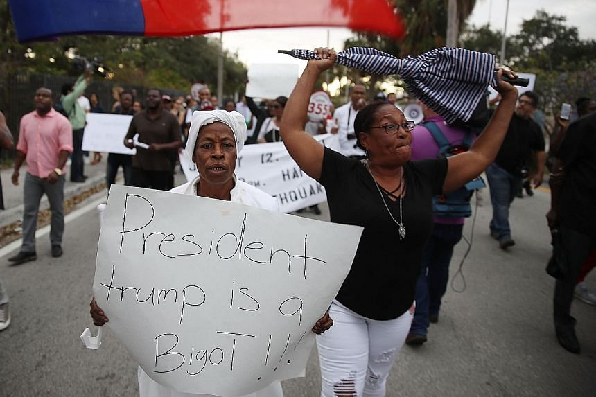 A demonstrator in Miami adds her view to the chorus of condemnation of President Donald Trump's reported statement about immigrants from Haiti, Africa and El Salvador.