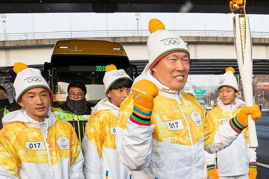 South Korean football legend Cha Bum Kun with the Olympic flame during the Pyeongchang 2018 Torch Relay near the World Cup Stadium in Seoul yesterday. The torch will be paraded for four days before making its way to Pyeongchang for the start of the W