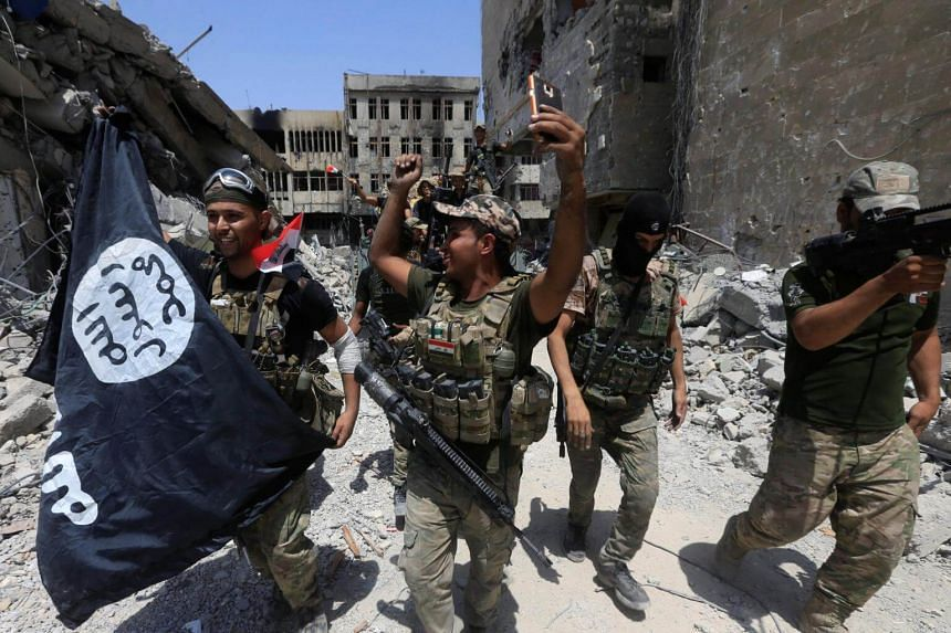 Members of the Emergency Response Division hold an ISIS flag which they pulled down, as they celebrate in the Old City of Mosul, Iraq on July 8, 2017.