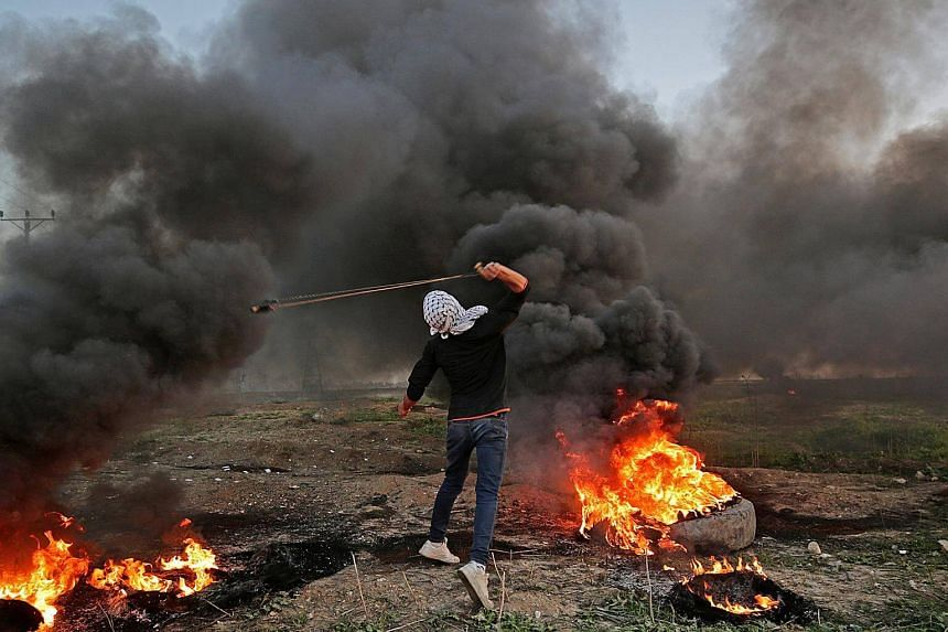 A Palestinian protester throws stones at Israeli troops during clashes  near the border in eastern Gaza City, on Jan 12, 2018.