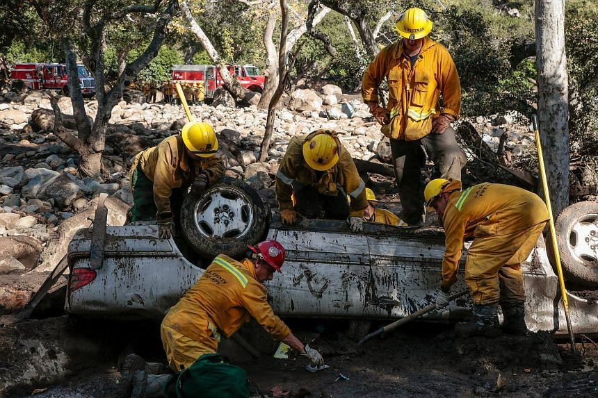 Rescue workers search cars for missing persons after a mudslide in Montecito, California on Jan 12, 2018.