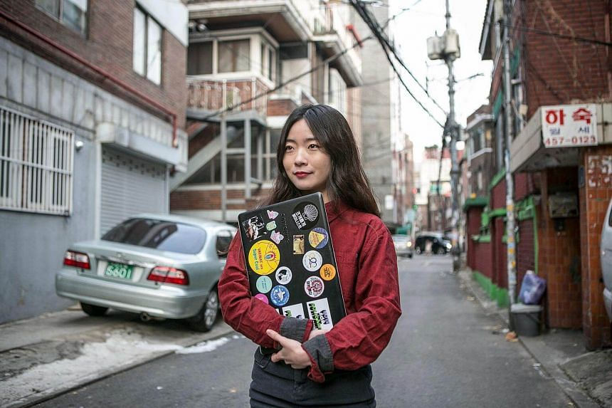 Lee Na Yeon, a philosophy major who had an abortion five years ago, holds a laptop case showing her support for women's causes in Seoul, South Korea on Dec 14, 2017.