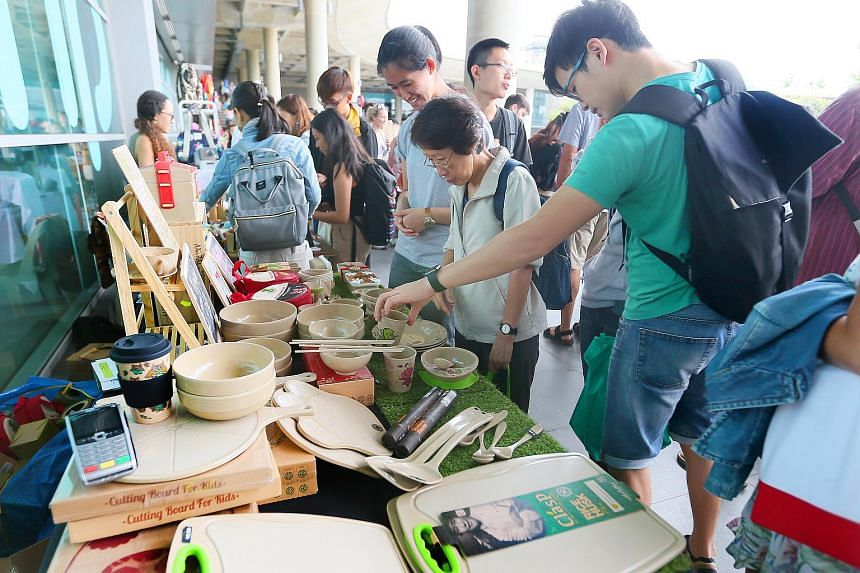 People looking at goods by Husk's Ware, which sells tableware and cutlery made entirely of rice husks, at EarthFest 2018 on Jan 14, 2018.