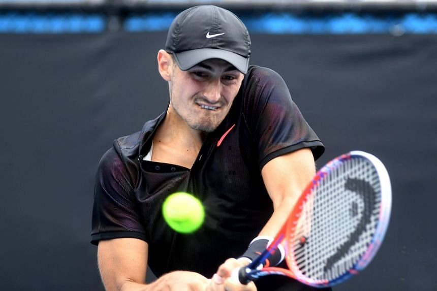 Bernard Tomic hitting a return to Lorenzo Sonego during a qualifying match for the Australian Open, on Jan 14, 2018.